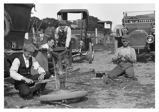 Four gentlemen working on the repair of the touring car at left.