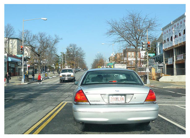 A Ford Crown Victoria registered with City Bicentennial plates stopped at a traffic light.