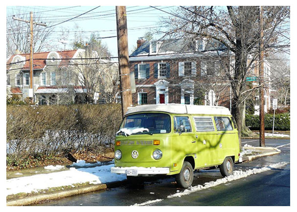 A Volkswagen camper parked on a residential D.C. street after a light snowfall.